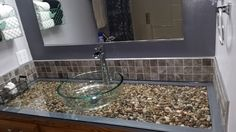 I built a tray for the vanity and put pebbles in, covered it with plate glass, tiled around it and added a glass vessel sink and waterfall faucet. Love how it t…