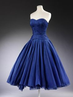 1951  The overlapping, curved pleats   fine, slightly stiff, silk fabric. The controlled movement on the curved, fitted bodice is achieved by the dextrous pleating of fabric cut on the bias, fronted with no visible seams.    The scalloped pleating encloses the front torso up to the low, strapless décolletage, and continues across the back in straight horizontal lines. The bodice fits the figure tightly to the hips and from there the skirt falls in long, soft pleats.