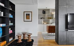 House tour: a sleek apartment in Portugal : The family room is divided into three distinct areas: an office area, a TV area and a reading area. Designs by de Carvalho (including the black iron bookshelves, palisander desk and wool-tencel rug) are accessorised with classic 'Eames' stools by  Charles and Ray Eames for Vitra and accessories by Anna Westerlund.