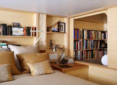 """The highlight of the remodeled apartment is the """"library"""" beside the bed. It is a tiny alcove in the wall, just big enough for one person to sit among the built-in shelves and flip through a favorite tome."""