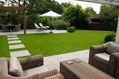 pelouse synthétique et pas japonais en dalles de pierre naturelle, pergola en bois massif et mobilier de jardin et rotin