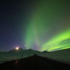 The Northern lights dancing over the Haines Highway as the moon sets behind Nadahini Mountain.  (photo: @andrewstrain via Instagram) #explorebc #explorecanada