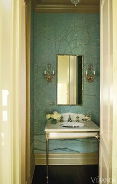Suzanne Kasler - Stunning powder room with turquoise Chinoiserie wallpaper framing French sconces flanking bamboo mirror over white marble washstand with Greek key sink over hardwood floors.