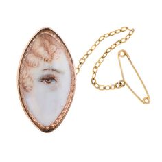 """Lozenge-Shaped Victorian Lover's Eye. A marvelous and rare example of the ever-popular lover's eye… this one, with a host of details adding to the charming mystery that surrounds these lovely artifacts. This piece is a unique """"navette"""" marquis shape, in 14k rose gold, depicting a redheaded woman and with a safety chain. c1880"""