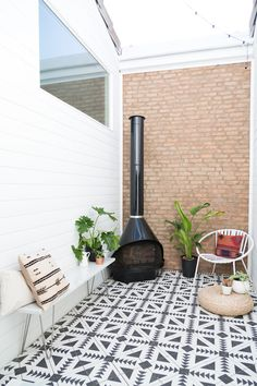 Love this tile flooring, vintage fire place, chair and potted plants.