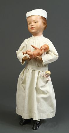 Commercially dressed as a male Doctor (white slacks under gown), possibly at a department store or doll's shop