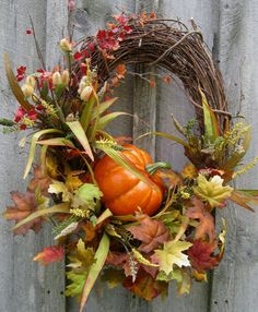 Fall Woodland Pumpkin Wreath  The fall wreath has a big harvest pumpkin, a flurry of fall leaves and a colorful assortment of fall flowers, berries and is topped off with a burlap deco mesh ribbon. The wreath measures approximately 24 inches across. Lovely.