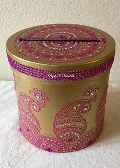 This is the listing for round shape gold color painted magenta color henna decorated with rhinestones and trim,to add sparkle and touch of bollywood glamour to your party decor. Create the perfect mood for every festive occasion with these boxes.Celebrate your taste and your style and use it in its original simple elegance or decorate it to fit any occasion or mood. You can also use it to create a one-of-a-kind centerpiece, Truly a must have item for indian/pakistani themed wedding decor...
