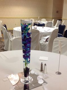 Tall pilsner vase with blue bom orchids submerged and a floating candle