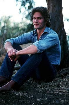 Patrick Swayze sitting on the ground leaning against a tree