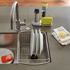 "Dry your dishes in the same place you wash them - the sink. Our Stainless Steel In-Sink Dish Drainer expands to fit over sinks up to 21"" wide. It holds plates and glassware vertically and flatware in a clear plastic caddy. Clear plastic tubing on the expanding arms prevents scratches on your sink and keeps the drainer from slipping."