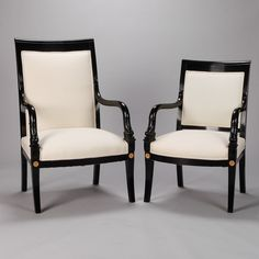 Pair His and Hers Ebonised Empire Style Dolphin Chairs With Brass Mounts  --  Late 19th century pair of upholstered his and hers chairs. Frames are made of ebonised mahogany with carved dolphin-form arms and decorative brass medallion mounts. Newly upholstered in muslin and ready for the fabric of your choice.   --   Item:  6368  --  Retail Price:   $4895