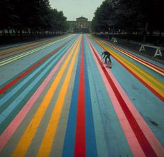 "Art-street photography of Philadelphia Artist Gene Davis putting finishing touches on his 414-ft-long painting ""Franklin's Footpath,"" painted on street in front of Philadelphia Museum of Art. / 1972 / Photographer: Henry Groskinsky"