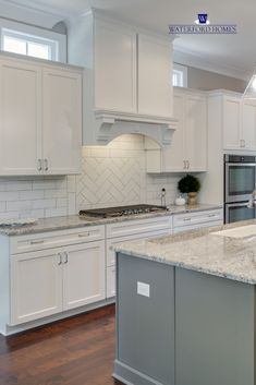 Traditional white kitchen with shaker cabinets. A neutral granite and gray kitchen island add contrast. Subway tile lines the walls with herringbone design behind the stove. Double ovens and a gas stove provide functionality. Kitchen Cabinets Grey And White, White Cabinets White Countertops, Grey Granite Countertops, White Granite Kitchen, Grey Kitchen Island, Shaker Cabinets, Kitchen Tile, Subway Tile White Kitchen, Gray Kitchen Walls