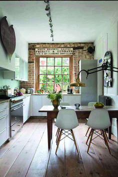 Colours. Wooden floor with white units and silver appliances, wooden table, exposed brick and industrial copper lamp