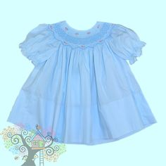 Rosalina short sleeved Bishop Dress with blue and white smocking and pink rosettes on the neck line.  Visit www.hidenseekboutique.com to order