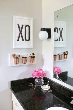 Bad mit schwarz-glänzendem Marmor-Waschtisch, pinken Blumen und kupferfarbenen Pinselbehältern ♥