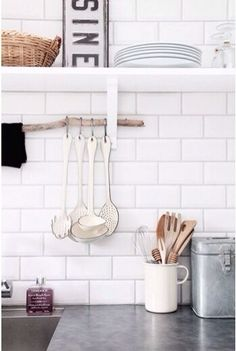 A few ways to store your cooking utensils when you don't have room in the drawers.The branch laying across the shelf supports was a clever idea. No need to attach hooks to the tiles that way.