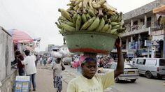 A Ghanaian woman carries a heavy load of bananas in Accra market