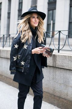 Perfect wavy hair, a super chic star embroidered bomber jacket, + cool camo wallet | Street Style from NYFW Fall 2016 @stylecaster