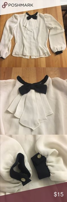 Tuxedo like chiffon long sleeve cropped blouse. Sheer cuteness with matching buttons on cuffs & down middle of back and poofed shoulders. Definitely sheer and looks great with a black tank. Tops