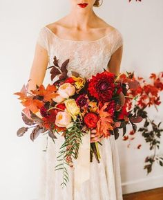 Orange And Red Fall Wedding Bouquet: Embrace autumn and use all the colors in your bridal bouquet. Use yellows, oranges and reds to capture the change from summer to fall. Include leaves in your bouquet if you want to add interesting texture.