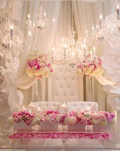 Sweetheart table with pink, blush & ivory flowers, crystal chandeliers.