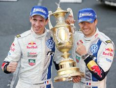 France's Sebastien Ogier (R) and co-driver Julien Ingrassia celebrate with the trophy after winning the Wales Rally GB, the final round of t. Rally Drivers, Giving Back, Victorious, Pilot, Captain Hat, Two By Two, Champion, Racing, Baseball Cards