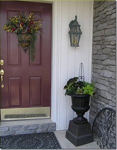 Burgundy front door with gray brick.