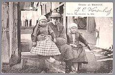 Marken vader met een jongetje naast hem en een meisje op schoot