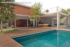 Deck em madeira desidratada sem verniz e a piscina revestida com pedras Hijau…
