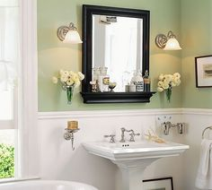 White wainscoting with pale green walls, black framed mirror & frames, white pedestal sink