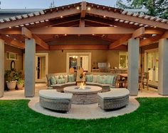 Exterior Design, Gorgeous Traditional Back Patio Designs With Plait Furniture Also Plait Pouffe Also Traditional Fireplace Design With Stones Fire Surround Also Charming Green Field Also Wooden Dinner Set: Back Patio Designs for Our Freshness House Design