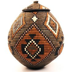 Africa | 'Ukhamba' basket woven by the Zulu people of South Africa | To create this traditional basket, weavers use strips of naturally waxy palm fronds wrapped around coils of wild grasses. Some baskets are still used for liquid storage in the rural areas of South Africa. Watertight baskets are readied by rubbing wet cornmeal inside. When liquid is added, the coils swell. Some leaks through, evaporates, and cools the contents.