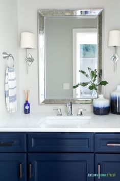 Powder bathroom with Benjamin Moore Hale Navy cabinets, chrome star sconces, antique silver mirror and Daltile One Quartz Luminesce color countertops. Walls are painted Behr Castle Path.