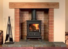Family Room wood burning stove decor - built to look like a fireplace Fireplace Pictures, Fireplace Logs, Cast Iron Fireplace, Fireplace Design, Fireplace Ideas, Brick Fireplaces, Cottage Fireplace, Fireplace Surrounds, Wood Burner Stove