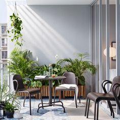 Varanda pequena com mesa dobrável em castanho escuro, quatro cadeiras empilháveis e floreira em acácia maciça com plantas verdes.