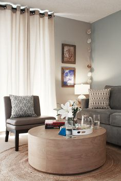 Nice living room -- especially grey and other neutrals, textured rug, ottoman/coffee table, and curtains.