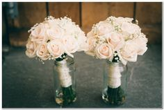 Bridesmaids bouquets of cream roses and white gyp or baby's breath .
