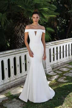 This crepe off the shoulder fit and flare gown features an illusion cut out at the bust adding a subtle hint of today's modern styling. For a more conservative look, the gown also available without the cut out.