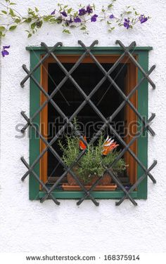Flower pot in a decorative window with bars - stock photo