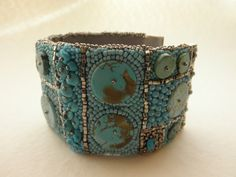 The bead embroidery uses Japanese and Czech glass seed beads, as well as several types of turquoise disks and nuggets.