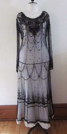 Vintage 1920s Flapper Era Sheer Beaded Dress Jet Black Glass Long Sleeves. It is black net covered in jet beads.  The work around the neck, shoulders and bodice is especially elaborate and beautiful.  The long sleeves flare at the wrist and also have extensive beading. Front