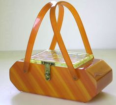 Buttery bakelite purse with diagonal striping effect. 2 handles and a subtly decorated lid.