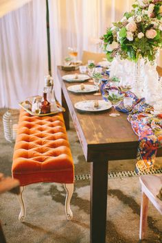 Boho Chic Table Setting.  I don't love the orange bench, but I do love the look  of a padded, tufted bench at the table in addition to chairs.