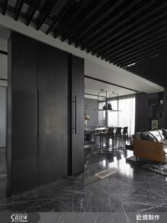 54.5 坪的空間,在開放式格局的規劃下,以一道長廊連貫了公、私領域,不僅形成流暢動線,也保有居家中對話的可能性;而在空間中,設計師刻意以低彩度作為鋪陳,同時添入不少天然材質,展現出沉穩、充滿力度的調性,而之中流通的空氣與光線,則讓粗獷氛圍中釋放出隱約的溫柔。  客廳以電視主牆作為視覺焦點,牆體採不加修飾的粗獷石材,搭配嵌牆鐵件層架,刻畫出整道牆面的立體輪廓,而在整體空間中,家具、天花格柵、大理石地坪皆呈現灰黑調性,但卻點綴少許溫潤木色,提升空間彩度;餐廳則不刻意界定領域,在開放格局中,巧妙陳列中島餐桌、調理吧檯位置,形成順暢動線,並在天花板上方設計懸吊餐櫃,打造輕盈視感;而餐桌後方則為書房空間,配置了移動拉門做出界定,讓閱讀領域保有彈性規劃;延伸入內則可來到寢臥區域,在床頭背景牆做出交織的細緻紋理,營造出沉穩的品味,床頭板則刻意降低並退離牆面,讓床頭牆的層次更加俐落完整,而睡眠區旁則配置白色櫃體,滿足了收納展示機能,同時,也形成從睡眠區過渡到更衣室的導引動線。  小編的最愛…