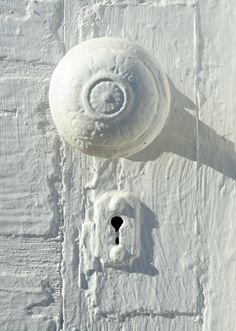 White door. I'd just love to strip off that door knob and key hole just to see the pattern and materials... ;)