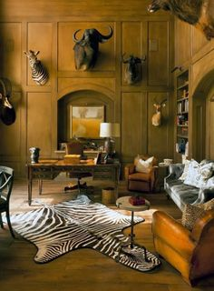 Well, if you have a hunter in the family, there's nothing nicer-looking on a paneled wall than art work in a fancy frame, or an over-sized animal 'trophy' from a hunt!  The zebra-skin rug is a great way to 'tie in' the wall decor to the room...
