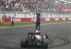 Red Bull Formula One driver Sebastian Vettel of Germany celebrates atop his car after winning the Indian F1 Grand Prix at the Buddh International Circuit in Greater Noida