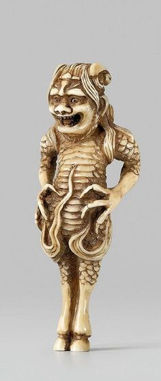 A rare ivory netsuke of a mountain god. Late 19th century The composite long-haired creature with the body of a snake stands upright on scaly legs with hooves and belly pushed forward. The scaly arms end in four-clawed hands and flames emanate from the joints. The humanoid head with opened mouth is all the more fierce for the deep-set eyes and the two curved horns.The carving is based on an illustration in the Sôken kishô